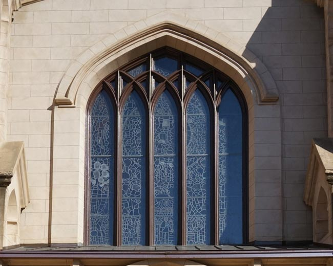View of exterior of building.  Stained glass window design is visible through clear glass protective exterior layer