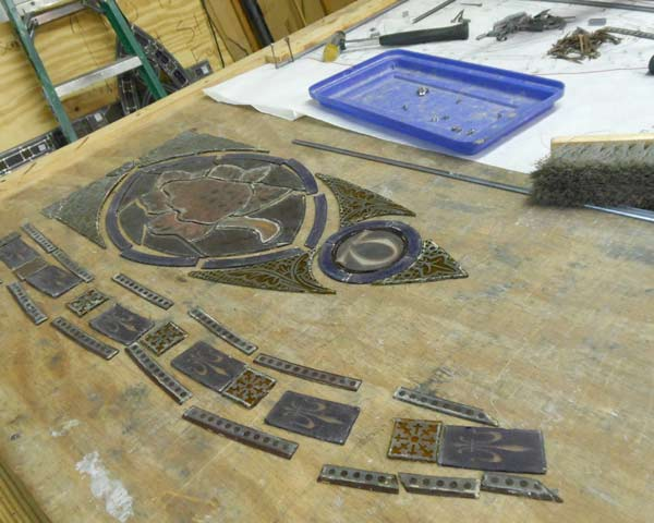 pieces of a stained glass window laid on a worktable to be re-leaded
