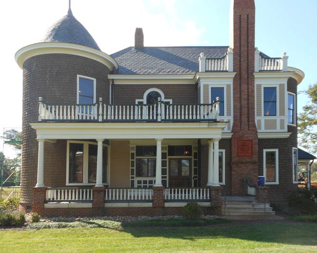 A large historic looking two-story brick home on a green lawn.  White wooden windows are on all visible walls, including in round-tower section of the house.
